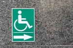 Confusing signage with International Symbol of Access wheelchair sign, in green with arrow. Is this an exit, entrance or toilet?