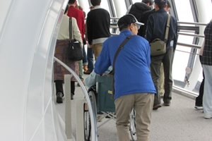 Elderly person in wheelchair being pushed up ramp at tourist Skytree observation tower in Tokyo