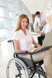Lady in office, using a laptop, whilst using a wheelchair