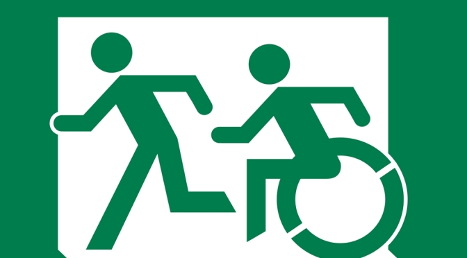 Large Exit Sign US Style, Accessible Means of Egress Icon wheelchair symbol and running man, moving left, White on Green