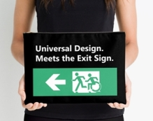Lady holding a bag with the Universal Design Meets the Exit Sign wording on it, with a green exit sign showing person running followed by a person using a wheelchair, moving in the same style as the running person.