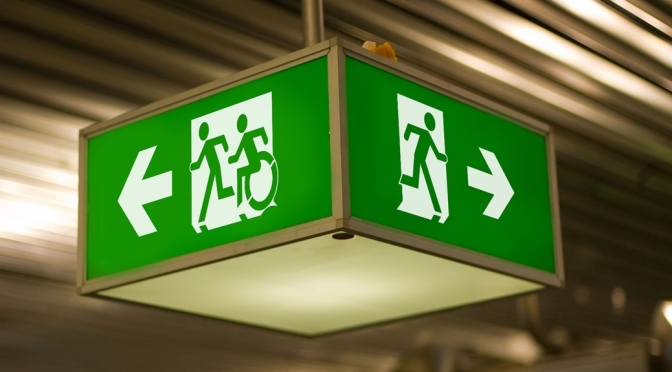 Universal Design Meets the Exit Sign, the Accessible Means of Egress Icon moving to the left with the Running Man, the Running Man type exit sign moving to the right