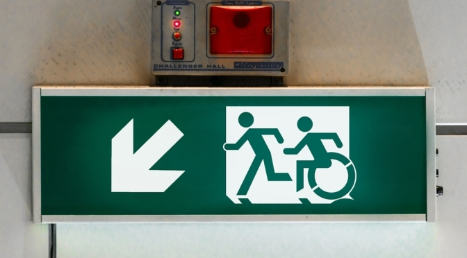 Universal Design Meets the Exit Sign Accessible Means of Egress Icon on wall mounted exit sign. Green exit sign showing a person using a wheelchair and running man moving to the left quickly through a doorway