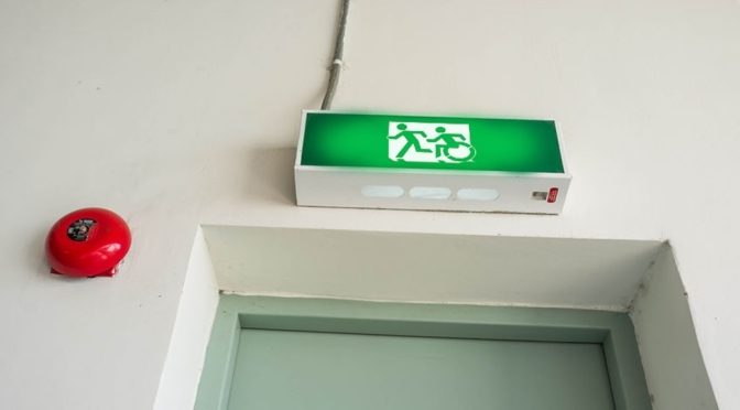 Universal Design Meets the Exit Sign Accessible Means of Egress Icon on an exit sign over a doorway. It shows a person running followed by a person using a wheelchair, moving in the same style as the running person, they are moving to the left through a doorway