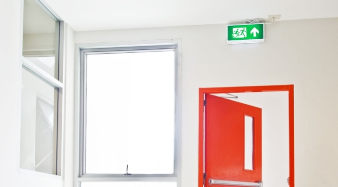 Universal Design Meets the Exit Sign with Accessible Means of Egress Icon green exit sign showing person running followed by a person using a wheelchair, moving in the same style as the running person, they are moving the left through a doorway, which is iinstalled over an open doorway