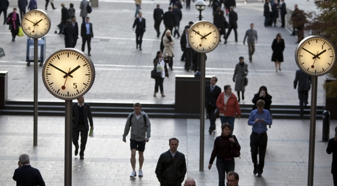 Analogue clocks suspended over people walking in train station