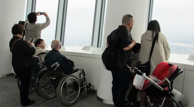 Elderly couple both in wheelchairs at tourist city Skytree observation tower in Tokyo, looking out of Tokyo city