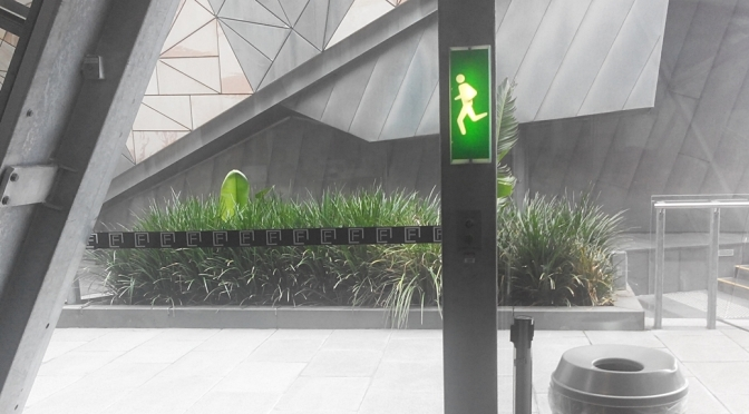 Federation Square Melbourne Running Man exit sign in vertical slim line design with alternate design for the running man pictorial element