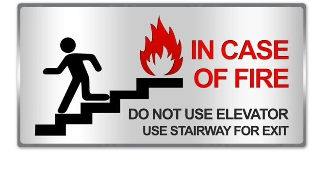 Signage for a stairway that shows a person running down the stairs with the words In Case of Fire Do Not Use Elevator Use Stairway for Exit