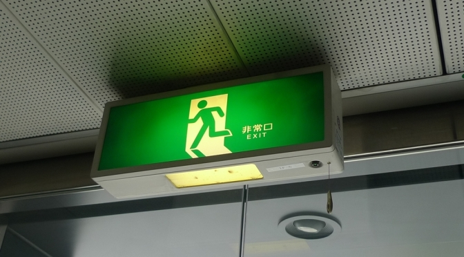 Japanese green exit sign with Running Man moving to the left through a doorway