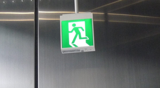 Japanese overhead small green exit sign with Running Man image moving through doorway