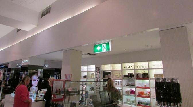 Exit sign in Melbourne Department store, suspended from ceiling over merchandise