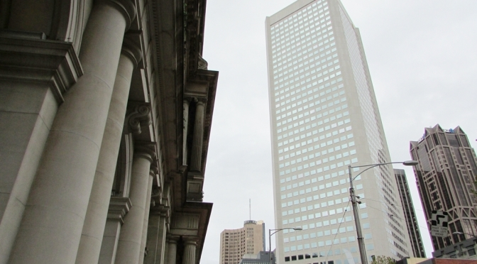 Melbourne Skyline with heritage style building with ornate columns to the left and a modern skyscraper to the right