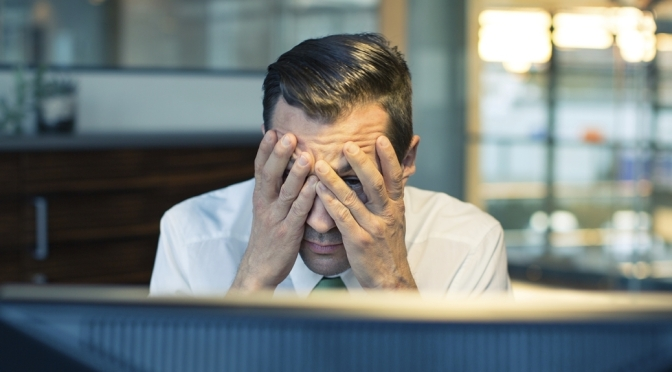 Stressed man with head in hands in front of computer